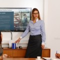 Global Mobility Solutions honored for its excellence in leadership training Leader Blonde woman with glasses, standing in front of screen, presenting to one man and three women how to Position Your Request for Proposal