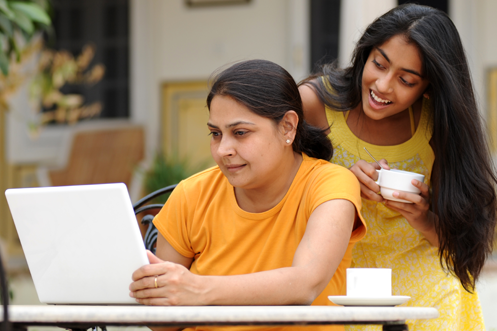 Two women in India using a computer to enter Online Portal Form C checkout dates