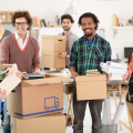 Two female and four male employees packing up boxes for a corporate relocation after confirming their business relocation budget