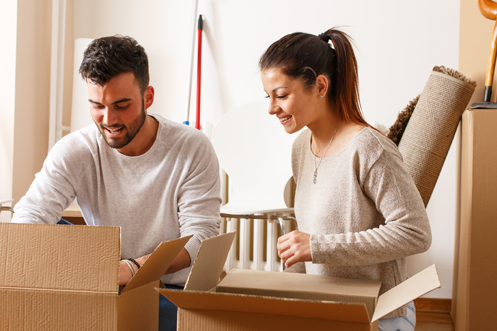 Employee Relocation or Workforce Mobility? Man with brown hair and beard, and a woman with a ponytail, packing brown cardboard boxes to prepare for a move, for her impending employee relocation and new employment assignment.