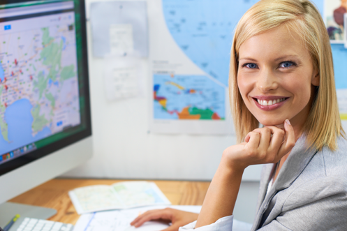 Blonde woman smiling, in front of computer monitor with a world map on the wall behind her, using MyRelocation Technology
