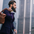 Business man with beard walking through Shanghai, carrying a leather bag, in country legally with China Working Visas and Work Permits