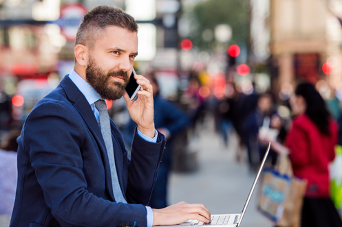 Man with beard holding a phone to his ear, in front of a laptop, in Piccadilly Circus in London, United Kingdom, wondering to himself what does the UK Economy look like for 2018