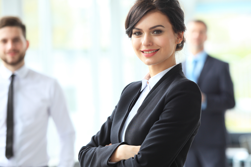 Woman executive with short brown hair and business suit smiling, co-workers behind her, all benefitting from technology trends that allow for global talent mobility