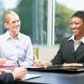 Woman in dark suit, short dark hair and smiling, discussing with one man with brown hair and one woman with blonde hair the Benefits to Outsourcing Relocation Programs