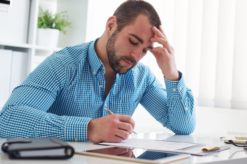 Man with beard in a blue checkered shirt, sitting at a desk, one hand on his forehead, filling out a Form I-9 with helpful nine tips