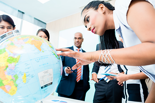 Woman with dark hair and white shirt looking at and touching a world globe, with one man and two women in the background also looking at the globe, as they consider outsourcing global relocation programs