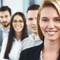 Close-up front view of mid 30's business team standing in line in their office. Focus on the closest person to the camera, smiling blond woman. There are five people total, two women and three men, as they consider Global Productivity and Employee Development Industry Benchmarking Studies
