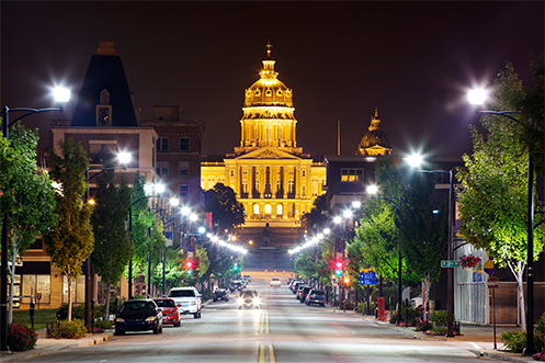 Best States Overall names Iowa as the number one state, Iowa State Capitol building lit up at night with a bank of streetlights highlighting the building looking like a strand of diamonds