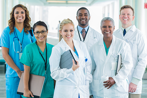 Four women and two men in healthcare uniforms, diverse races, diverse ages, diverse looks, smiling, standing together, happy because they have benefitted from healthcare industry relocation trends