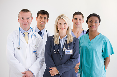 Five smiling male and female multi-ethnic medical personnel in varying dress like hospital smocks and doctor overcoats, facing forward, all leveraging relocation benefits to attract and retain talent in healthcare