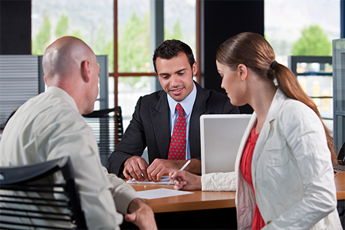 Woman in white coat and red shirt signing job acceptance papers, husband is next to her with white shirt, across from man in dark suit with red tie, take a job offer at Challenging Locations