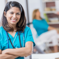 The Rise in Short Term Assignments in Healthcare with a smiling Asian woman, dark hair, arms crossed, in a doctor's office