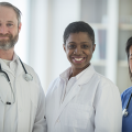 Handsome man with beard in doctor's coat with stethoscope, two attractive women in healthcare uniforms, all three smiling as they consider relocation program models for healthcare