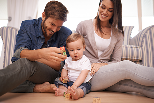 Family Matters and Career Support for Spouses Impacted by Relocations smiling man with brown hair and beard wearing blue shirt, holding toy blocks, playing with child, woman with long brown hair next to him, smiling looking down at child, wearing tan sweater over white tank shirt