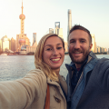 Blonde woman and handsome man with brown hair and beard, smiling in front of the Shanghai city skyline in the background, as they benefit from Shanghai Streamlines Foreign Expert Residency