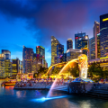 Singapore skyline at night, lion fountain streaming water into bay, named most livable city