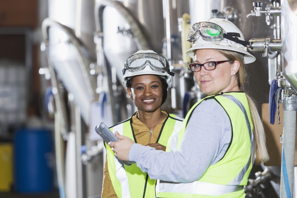 Two multiracial women working together in a manufacturing plant, standing in front of steel storage tanks. They are wearing white hardhats with safety goggles, and yellow reflective vests, looking at the camera, smiling.