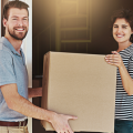 Smiling man with brown hair and beard, holding a cardboard box with a woman, he is glad for the Benefits of Pre-Decision Services which helped him determine to take a relocation assignment