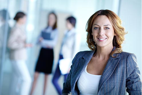 Woman with long hair, wearing blue jacket and white shirt, smiling, facing front with three other women in background, thinking about how to Recruit Top Talent