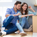 Handsome man with brown hair and beard, woman with brown hair, sitting on floor around moving boxes, looking at a computer to confirm their Traditional Temporary Housing