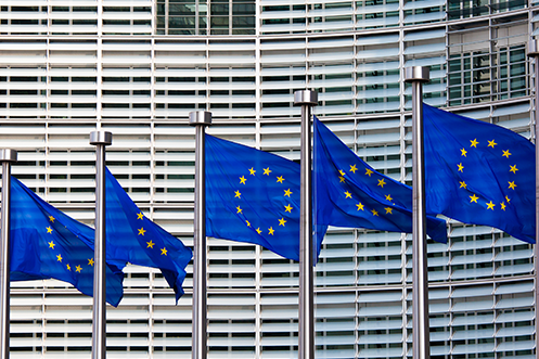 EU Flags on flagpoles flying in front of building, denotes residency rights