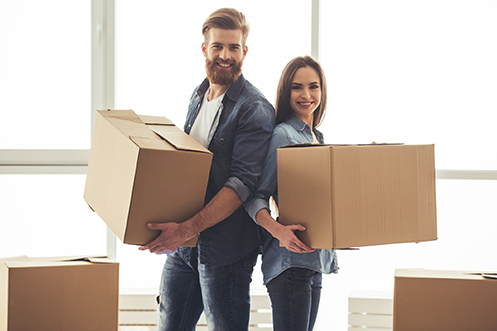 Handsome man with full beard holding a moving box, wearing a white t-shirt and blue shirt, standing next to woman with dark hair holding a moving box, happy their company chose to engage their RMC early in the relocation process