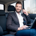 Handsome man with brown hair, mustache, and beard, riding in car, phone to ear, laptop open, smiling, talking about his company's Expedited Bidding Process