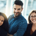 Woman with curly brown hair smiling, man standing with brown hair and beard and blue shirt smiling, and woman with blonde hair and glasses smiling, all are the new Mobility Manager for their companies