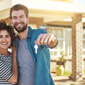 Handsome man with brown hair and full beard holding keys to a house, with a big smile, wearing a gray t-shirt and blue jean shirt over the t-shirt, woman with dark hair standing to his left, able to buy house because employer gave home purchase benefits to Encourage Transferees to buy a home instead of rent