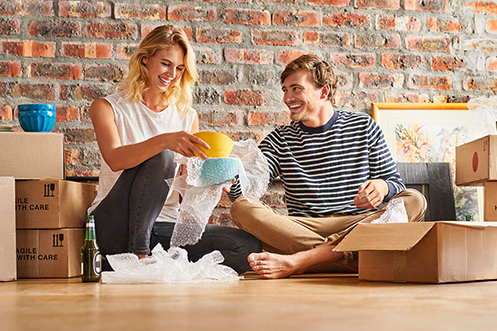 Blonde woman sitting on floor wearing white shirt, unpacking dishes, smiling, handsome man with brown hair, mustache and beard, sitting, smiling, looking at woman, wearing striped shirt, barefoot, as they go through household goods moves