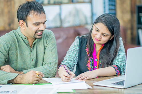 Man wearing green shirt, smiling, with dark hair, and woman wearing shirt with green sleeves and black vest, smiling, with dark hair, both are from India, filling out paperwork for immigration that is subject to increased premium processing fees
