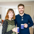 Woman with shoulder length hair and flower shirt, smiling, holding coffee mug, to left, and handsome man wearing blue sweater, smiling, with brown hair, mustache and beard, holding coffee mug, to right, thinking about their UK home and annual price growth decline