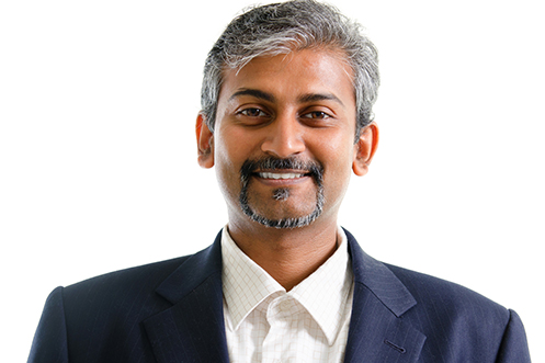 Handsome India businessman with black and gray hair, mustache and goatee, facing front, smiling, wearing a white shirt and blue jacket, grateful for ruling by India's Supreme Court