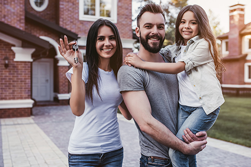 Happy family is standing with keys from their new house in hand. Smiling and looking at camera. Woman with long dark hair and white t-shirt. Handsome man with beard and gray t-shirt. Young girl with long brown hair and white shirt. The family got a new mortgage loan to buy their home
