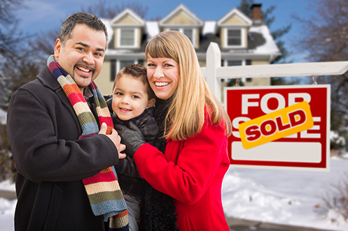 Man in coat with colorful scarf, black hair, mustache and goatee, small child, woman with blonde hair, all smiling, standing in front of house with a sold sign next to them, showing they bought this house from the home sellers