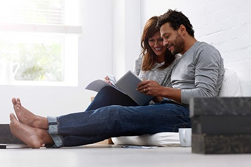 woman with long hair and man with short curly hair and beard, wearing jeans, barefoot, sitting on floor together, smiling, looking through their relocation documents prior to their home's relocation appraisal
