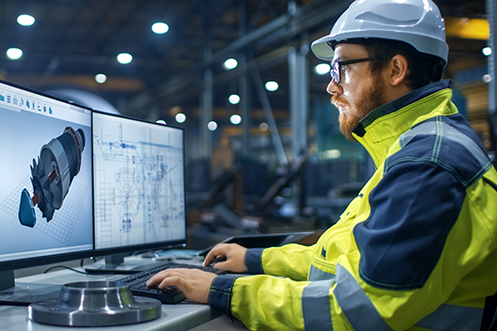 Handsome man with beard, glasses, wearing white safety helmet, looking at a computer screen in a factory, benefitting from his education, having no skills gap