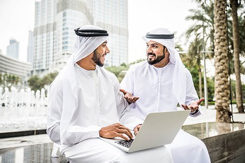 Two handsome Arabic businessmen in Dubai, smiling, talking, one holding a laptop, sitting outside in front of skyscraper, talking about how they can be successful in spite of the upcoming skills gap