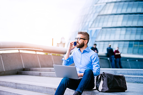 Handsome male job seeker with beard and glasses, talking on phone, sitting on steps in front of office building, with laptop open and briefcase next to him, looking into UK job openings
