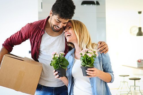 Man with curly hair, beard, red shirt, smiling holding moving box, arm around woman with blonde hair, blue shirt, smiling, holding flowering plants, busy with relocation, overcoming challenges