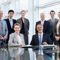 Five male and three female business people, all dressed nicely, one woman is seated, one man is seated, all are smiling, facing front, all are working at a corporate headquarters
