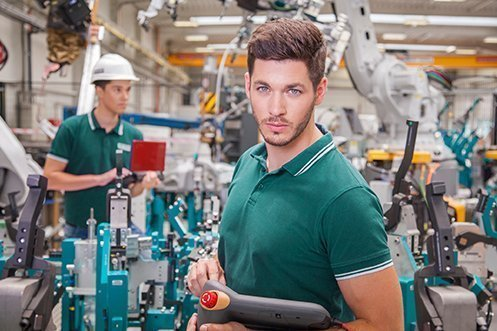 Handsome man with brown hair, mustache, and beard, wearing green shirt, working in a German factory, was one of the foreign job seekers who had skills and found a good job