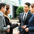 Two business men and two business women in China, all dressed in formal business attire including suits and ties, making proper introductions with business cards in an effort to develop good guanxi
