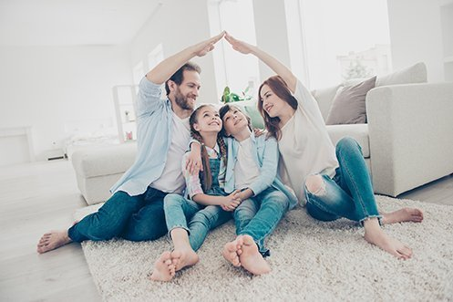 Handsome man in blue shirt and jeans, brown hair, beard, smiling, woman in white shirt and jeans, long red hair, smiling, both reaching over to touch their hands in a roof format over their two children in their new house they purchased using new real estate business models