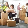 Planning team consisting of moving worker man in yellow jacket, office designer woman with design plans sitting in chair, man in dark shirt opening a cardboard moving box, woman in white shirt helping to open the cardboard moving box, all of them helping a company planning to relocate