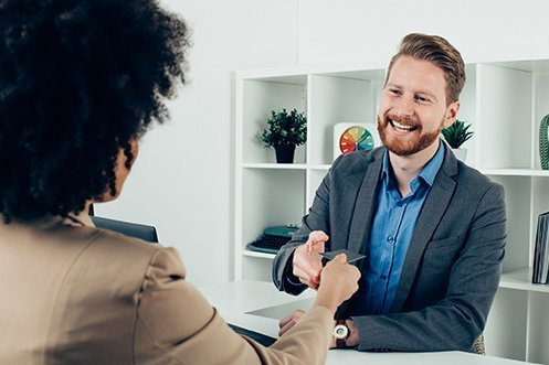 African American woman facing man, handing her business card to him, interviewing him for a position at a company, man is smiling, with beard and mustache, wearing blue shirt and gray jacket, during low 2019 unemployment