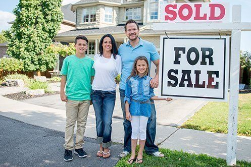 Young boy in green shirt, woman in white shirt with long dark hair, handsome man with beard wearing light blue shirt and white sandals, young girl in dark blue shirt, standing next to For Sale and Sold sign, family members in front of home they purchased through a relocation company's buyer value option program