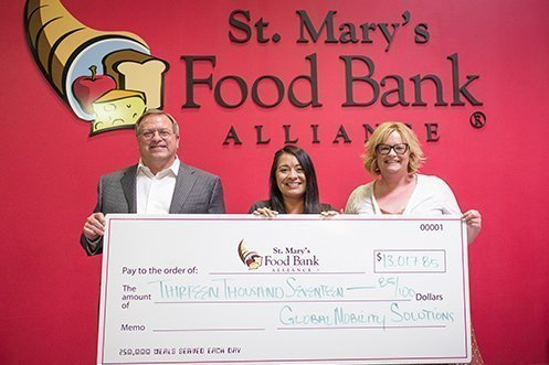 events Steven R. Wester, President (left), and Ann Knapp, Director of Transportation Services (right), present a check from Global Mobility Solutions for 2018 and 2019 Forum donations to Genevieve Villegas, Corporate Giving Officer (center), St. Mary's Food Bank Alliance.
