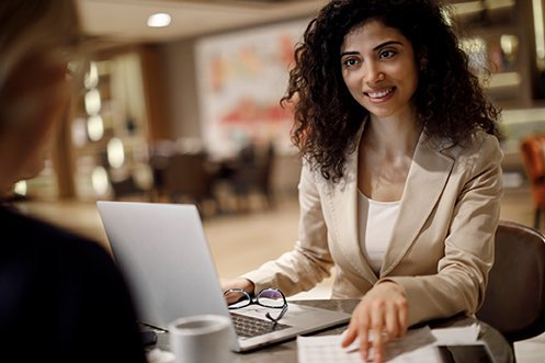 Woman with curly hair, white shirt, and tan jacket, facing forward, smiling, working with her expense management program